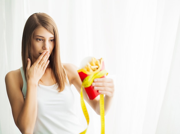 女性の不健康なジャンクフードを保持している体重計で体重を測定