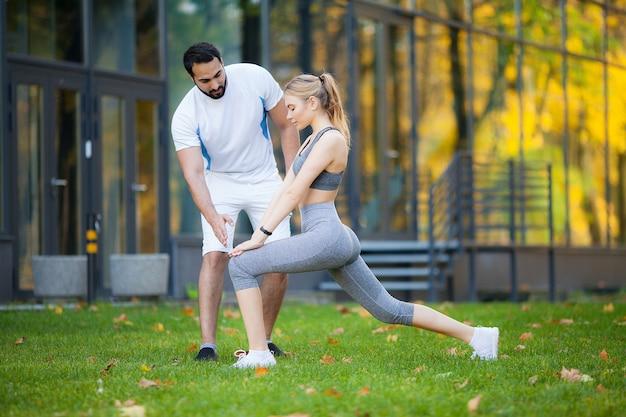 フィットネス、パーソナルトレーナーは、女性が屋外で運動しながらメモを取る