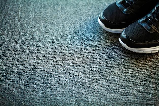 家の床に新しいスタイリッシュな黒のスニーカーのペア