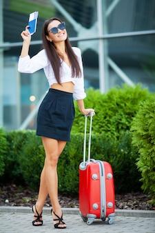 Молодая жизнерадостная женщина с чемоданом.
