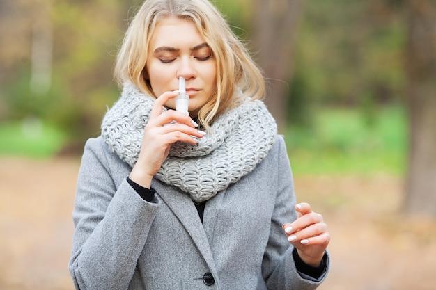 風邪やインフルエンザ。病気の若い女性は外の通りで鼻スプレーを使用します。