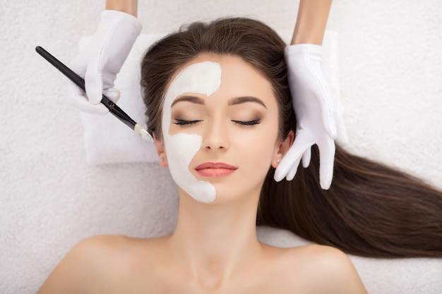 ビューティーサロンで顔のマスクを持つ若い女性のためのスパ療法