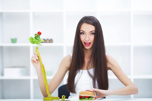 健康食品とジャンクフードの間を選択する美しい若い女性