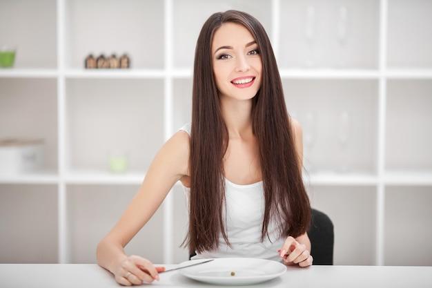 拒食症に苦しんでいます。フォークにエンドウ豆を入れようとしている女の子の画像