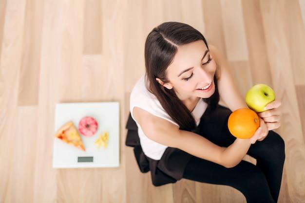 スケールと青リンゴとオレンジのスポーティな女性