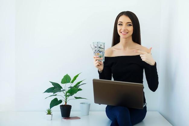 ビジネス。お金の手で保持している美しいビジネス女性。ビッグライトオフィスのテーブルに座って、コンピューターで動作します。幸せな少女は自宅で働きます。高解像度