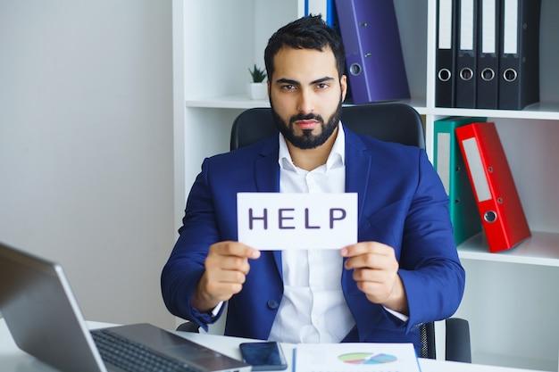 Бизнесмен в костюме и галстуке, сидя на рабочий стол, работая на ноутбуке компьютера с просьбой о помощи с картонной табличкой