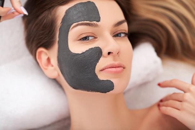 スパ。彼女の顔に粘土マスクを持つ魅力的な面白い女性