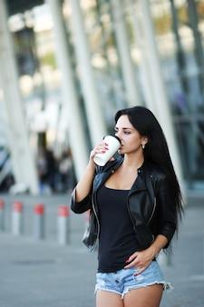 若い美しい女性は事務所ビルの横にあるコーヒーを飲む