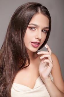 フェイシャルケア。目の下の皮膚に化粧品クリームの滴を持つセクシーな若い女性の肖像画
