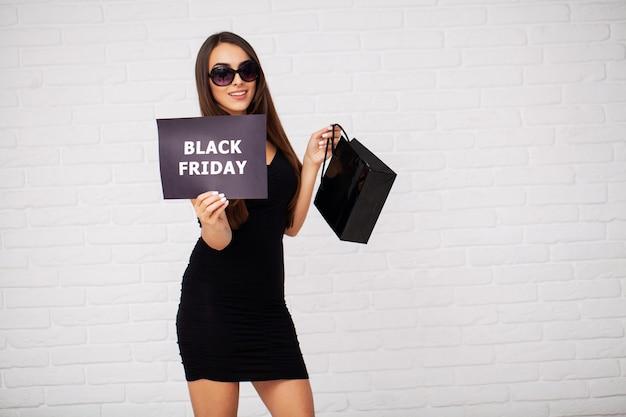 ショッピング。黒い金曜日の休日にライトに割引ブランクを保持している女性