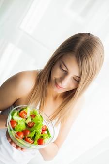 ダイエットと健康的な食事。トレーニングの後ヘルシーなサラダを食べる若い女性