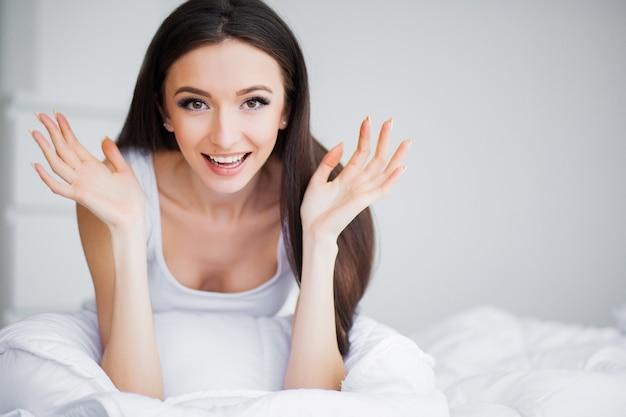 おはようございます。白いベッドでリラックスした笑顔のかなり若いブルネットの女性の肖像画