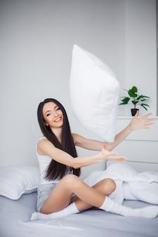 Выстрел из молодой женщины, сидя на кровати