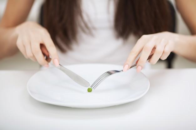Расстройство пищевого поведения. девушка держит тарелку и пытается положить горох на вилку