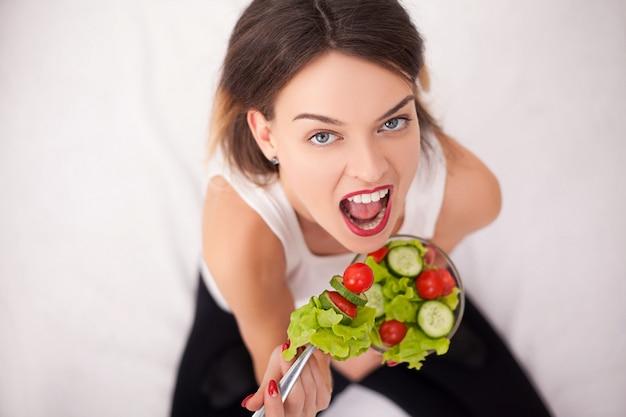 トレーニングの後ヘルシーなサラダを食べる若い女性