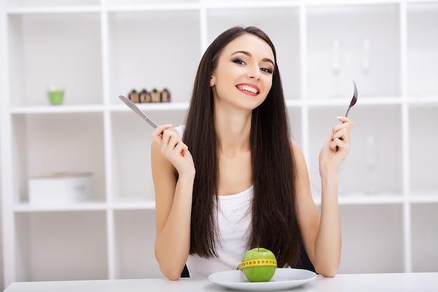 Диета, зеленое яблоко на белой тарелке, вилка, нож, потеря веса, здоровое питание, желтая измерительная лента, потеря веса