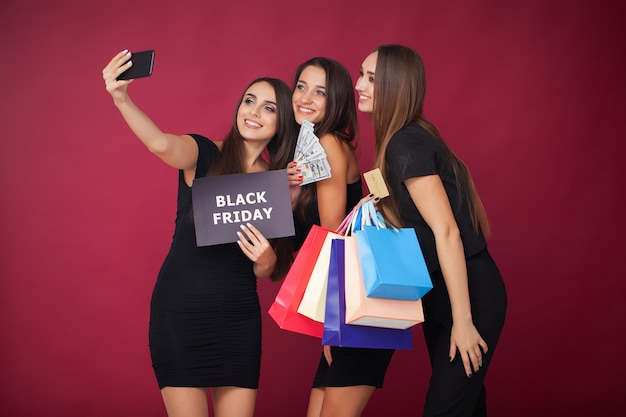 Элегантная брюнетка в черном платье с сумками для покупок, черная пятница