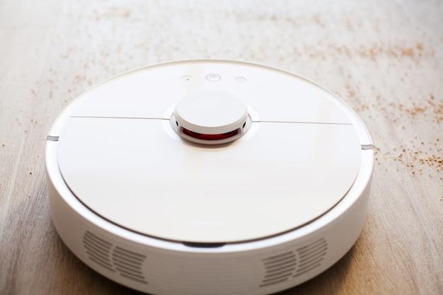 Робот-пылесос выполняет автоматическую уборку квартиры в определенное время. умный дом.