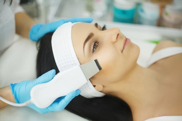 スキンケア。超音波キャビテーションの顔の剥離を受ける美しい女性のクローズアップ。超音波皮膚洗浄手順。美容トリートメント。美容。ビューティースパサロン。
