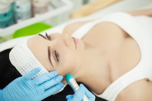 現在の治療を使用して皮膚療法を楽しんでいる美容スパで横になっている少女