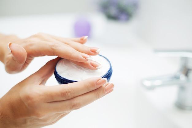 Закрыть руки использовать средства по уходу в светлой ванной
