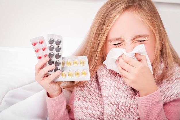 風邪やインフルエンザ。彼女の手に丸薬を持つ少女