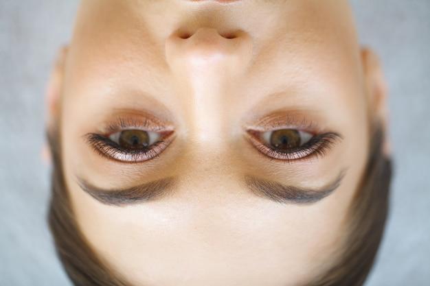 Крупным планом вид глаза голубой женщины с красивыми золотыми оттенками и черный макияж подводка для глаз. классический макияж. идеальные брови. студийный снимок