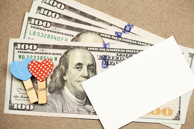 心、お金、空白の白いグリーティングカードで装飾的な洗濯はさみ