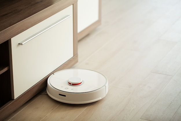 Пылесос-робот работает на деревянном полу в гостиной.