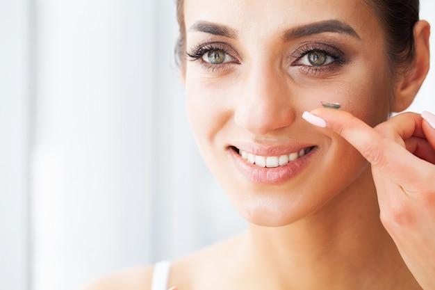 Молодая женщина носить контактные линзы