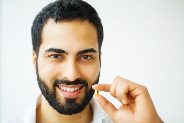 Красивый мужчина принимает таблетки