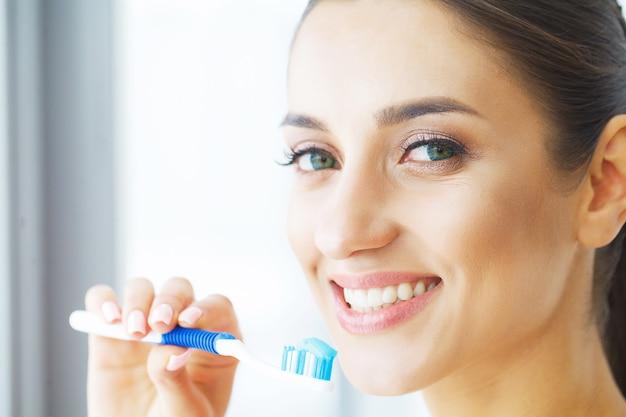 Женщина чистит здоровые белые зубы щеткой.