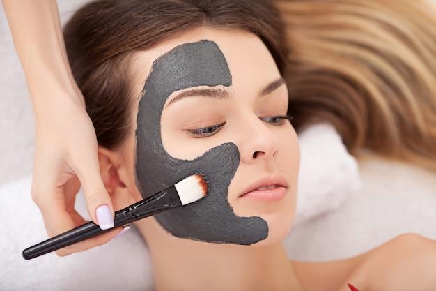 ビューティーサロンで顔の治療を得る美しい若い女性