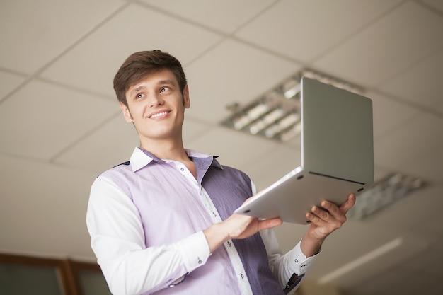 オフィスに立っている間ラップトップを使用して青年実業家