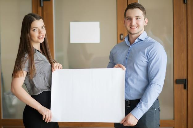 Деловые партнеры работают вместе и держат пустой белый плакат