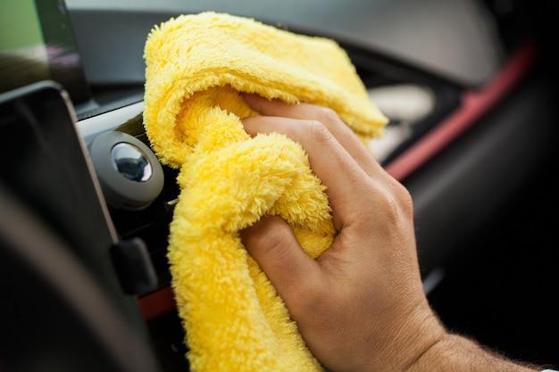 黄色のマイクロファイバーで高級車のパネルを拭く