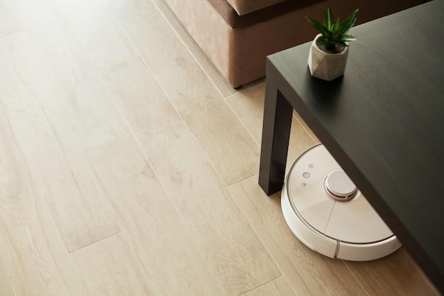 掃除機ロボットは、リビングルームの木製の床で実行されます。