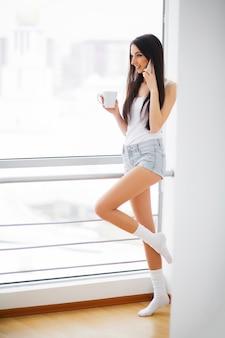 Красивая женщина, стоящая возле окна