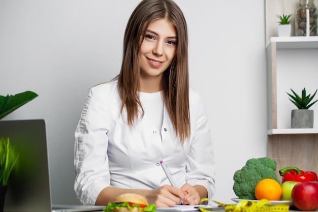 Женский диетолог с фруктами, работающих на ее столе