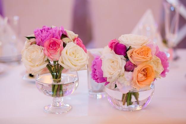 豪華な結婚式のイベントのためのレストランでのピンクと白の花のアレンジメント
