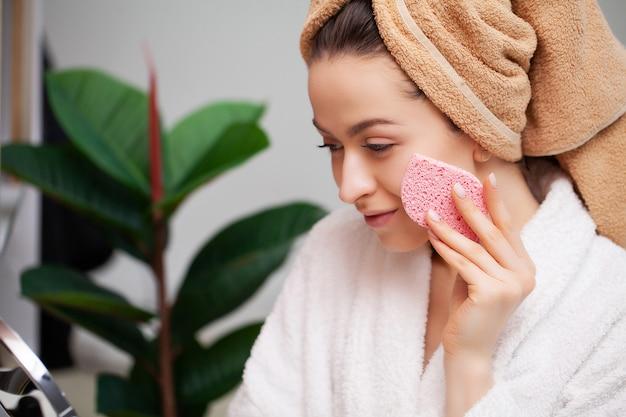 Симпатичная девушка делает макияж в лицо в ванной