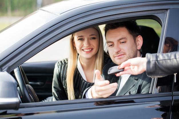 幸せなカップルが新しいモダンな黒い車を買う