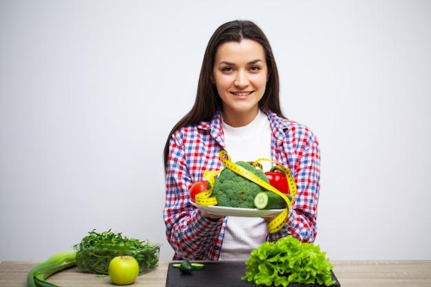 Концепция здорового питания и диеты, девушка держит овощи на фоне белой стене