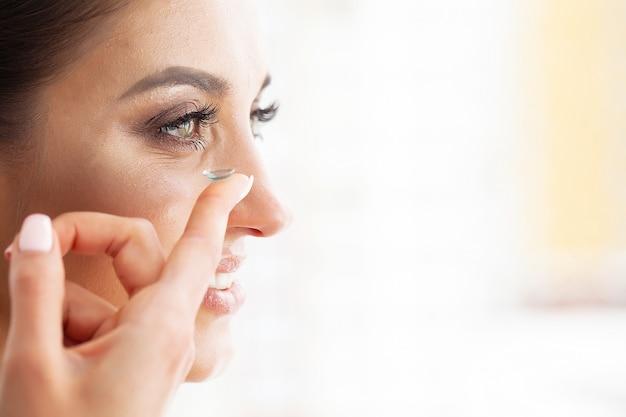 健康。若い女の子が手にコンタクトレンズを保持します。緑色の目とコンタクトレンズを持つ美しい女性の肖像画。健康的な外観高解像度