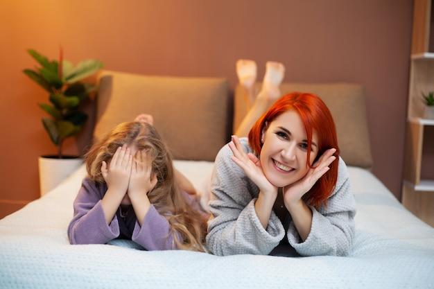 Мама и дочь отдыхают в постели у себя дома