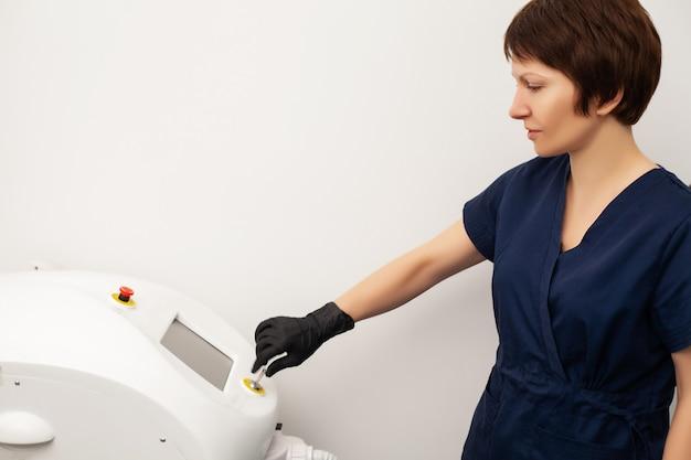 美容師の医師は、美容スタジオでクライアントをレーザー脱毛する準備をします