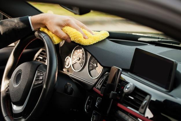 Уборка автомобиля. рука с салфеткой из микрофибры для чистки салона автомобиля