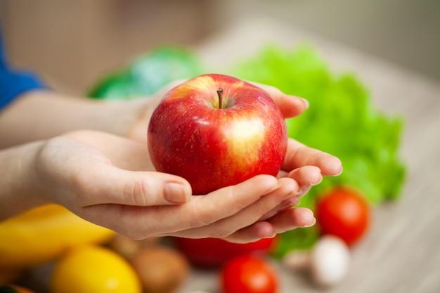 リンゴを保持しているテーブルで女性