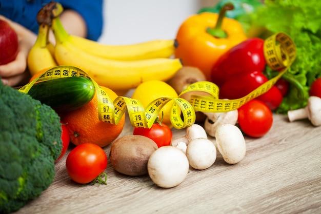 Полный стол свежих овощей и фруктов с желтой рулеткой